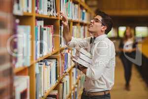 Nerd searching book while girl walking to him