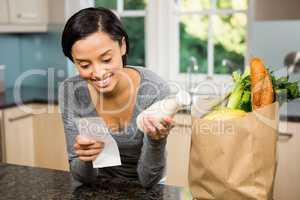 Smiling brunette holding receipt and milk