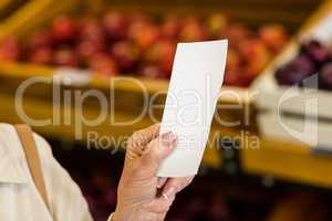 Female consumer holding a receipt