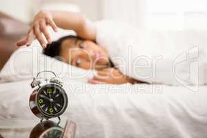 Alarm clock against brunette on bed