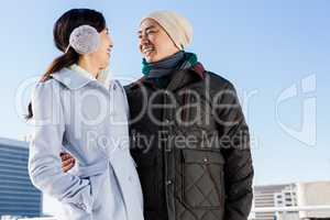 Happy couple in warm clothing looking at each other