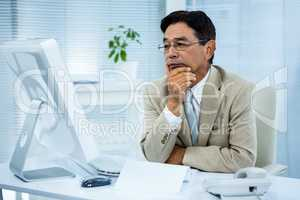 Undecided businessman at his computer