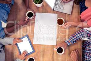 Professionals using technologies while holding coffee cups