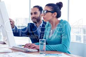 Serious businessman and businesswoman discussing over computer