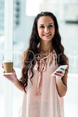 Smart woman using smartphone holding disposable cup