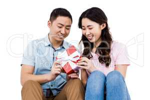 Cheerful couple holding gift box