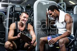 Muscular man discussing performance with trainer