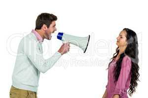 Screaming man holding loudspeaker with girlfriend