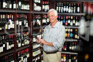 Smiling senior man choosing wine