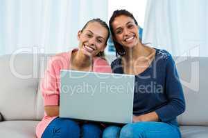 Friends using laptop on sofa