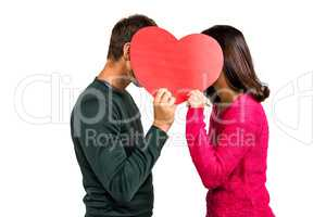 Couple covering faces with heart shape