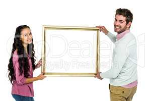 Smiling couple holding picture frame