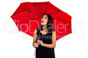 Shocked woman looking up while holding red umbrella