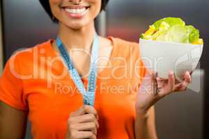 Smiling brunette with tape measure around neck holding bowl of s