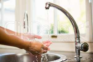 Mid section of woman washing hands