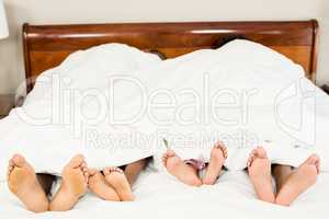 Parents and kids feet at the end of the bed