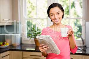 Standing brunette holding cup and newspaper