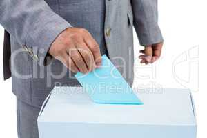 Businessman putting ballot in vote box