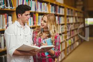 College students reading book together