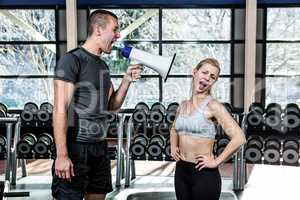 Male trainer motivating fit woman with megaphone