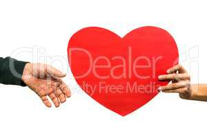 Cropped hand of woman giving heart shaped paper to man
