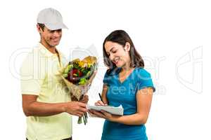 Flower delivery man taking signature of beautiful woman