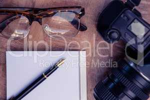 Pen on paper by camera and eye glasses at table