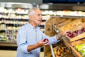 Senior man choosing onions carefully