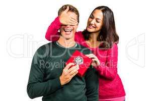 Smiling girlfriend closing eyes of boyfriend