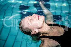 Relaxed woman floating in the swimming pool
