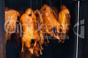 Smoked ducks hang on peg