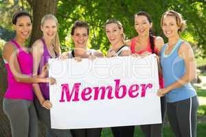 Member against fitness group holding poster in park