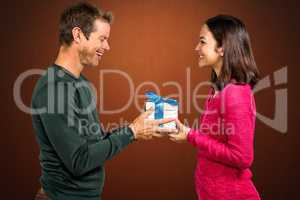 Composite image of girlfriend taking gift from boyfriend