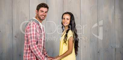 Composite image of smiling couple holding their hands and lookin