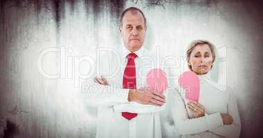 Composite image of older couple standing holding broken pink hea