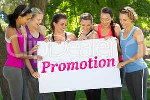 Promotion against fitness group holding poster in park