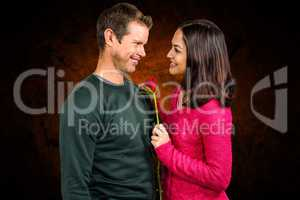 Composite image of smiling couple with red rose