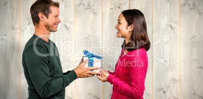 Composite image of smiling couple holding gift box