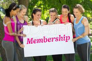 Membership against fitness group holding poster in park