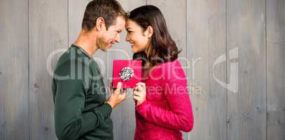 Composite image of cheerful couple holding gift box
