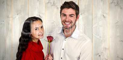 Composite image of smiling couple with rose