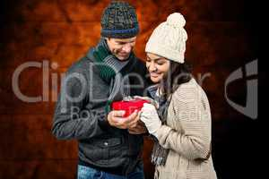Composite image of festive couple exchanging a gift