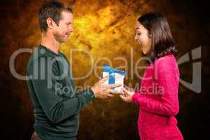 Composite image of excited girlfriend taking gift from boyfriend