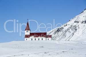 Church of Vik in wintertime with snowy mountains, Iceland
