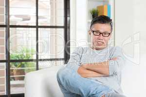 Mature 50s Asian male sitting at home.