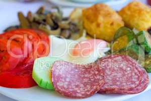 Sausage and scrambled eggs with owoseni on the plate.