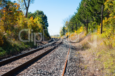 Train tracks curving left with telegraph poles on right