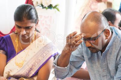 Hindu man putting tilak