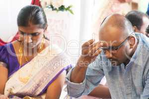 Hindu man putting tilak