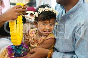 Baby girl received flower garland from priest.